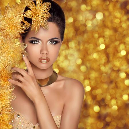 Glamoureuze mode schoonheid meisje portret. Mooie jonge vrouw met gouden bloemen op vakantie bokeh achtergrond verlichting. Luxe kapsel, make-up, accessoires.