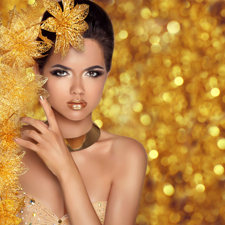 Glamorous beauty fashion girl portrait. Beautiful Young Woman with golden flowers over holiday bokeh lights background. Luxury Hairstyle, makeup, accessories.