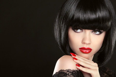 woman hairstyle: Stare. Fashion model girl face, beauty woman make up and red manicure. Bob black hairstyle. Brunette woman posing over black background. Stock Photo