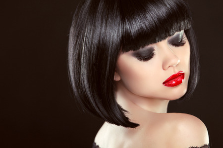 Smoky eyes makeup closeup. Black bob hairstyle. Sexy red lips. Brunette girl with shiny glossy short hair over dark background. photo
