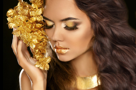 Golden makeup eyes closeup. Beautiful young woman in gold with flowers isolated on black background. Long brown hair.