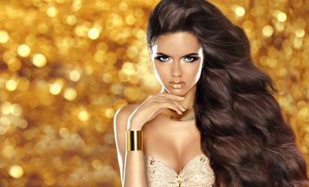 pelo castaño claro: Chica morena de moda con el pelo ondulado largo, maquillaje de belleza, joyería de lujo. Hermosa mujer joven y atractiva en vestido posando sobre vacaciones luces de fondo brillo.