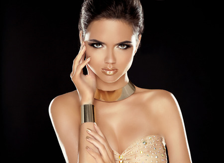 Fashion Beauty Girl with Golden Jewelry. Vogue Style. Glamour Lady. Luxury Woman Portrait. photo