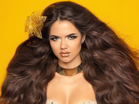 christmas perfume: Long wavy hair. Fashion Beauty Girl Portrait Isolated on yellow Background. Glamour Makeup. Gold Jewelry. Hairstyle.