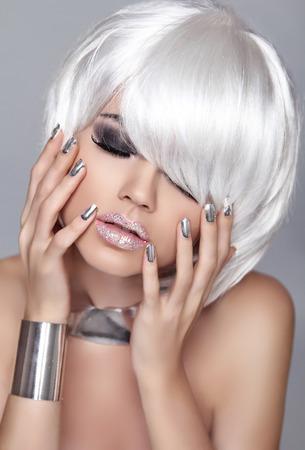 Fashion Blond Girl. Beauty Portrait Woman. White Short Hair. Isolated on Grey Background. Face Close-up. Manicured nails. Hairstyle. Fringe. Vogue Style. Stock Photo