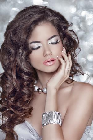 labbra sensuali: I capelli lunghi ondulati. Bella donna bruna con labbra sensuali, trucco, acconciatura