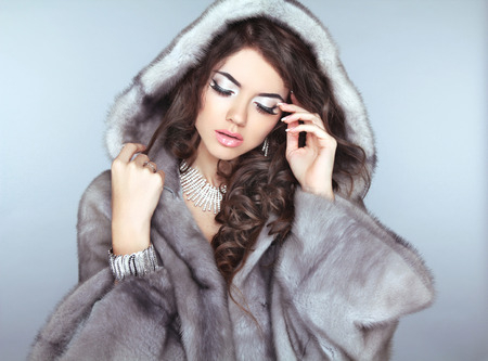 Beauty Fashion Model Girl in Fur Coat, Beautiful brunette woman with wavy hair and makeup. photo