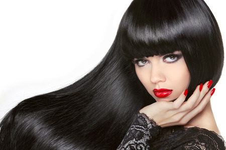 hair studio: Long Hair. Beautiful Brunette Girl. Healthy Black Hairstyle. Red lips. Makeup. Manicured nails. Beauty Model Woman isolated on white background. Stock Photo
