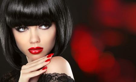 l  ¡piz labial: Portait modelo muchacha de la belleza de la Moda. Maquillaje y u�as pintadas de color rojo. Bob peinado negro. Mujer morena posando sobre fondo negro.