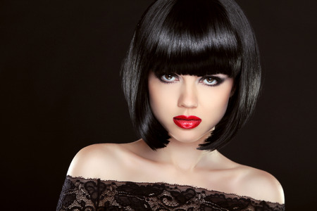 Black bob hair. Fashion model girl face. Brunette woman with red lips and short hairstyle over dark background.