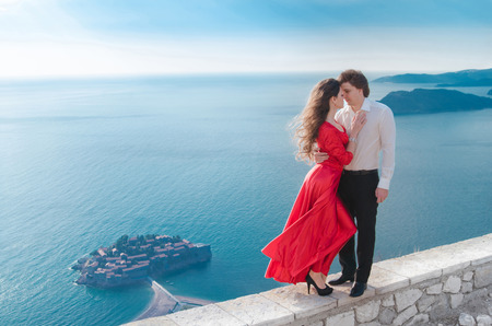 Romantic embracing couple beside blue sea. Love. Fashion girl in red dress with handsome man  in front of Sveti Stefan, Montenegro. Young woman with her groom. Travel. Vacations. photo
