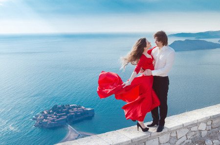 Young happy couple in love outdoor, Sveti Stefan, Montenegro. Attractive girl with blowing dress embracing her boyfriend over seaside photo