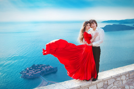 girl in red dress: Romantic young couple in love. Fashion girl model in blowing red dress with handsome man   in front of Sveti Stefan, Montenegro. Beautiful woman with her groom. Travel. Vacations. Stock Photo