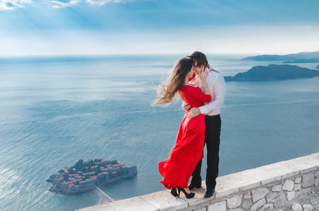 Romantic embracing couple beside blue sea in front of Sveti Stefan, Montenegro. Young woman with her groom. Travel. Vacations. Fashion girl in red dress with handsome man.