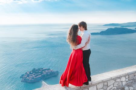 jovenes enamorados: Joven pareja romántica en el amor sobre fondo orilla del mar. Modelo de la chica de moda en la voladura de un vestido rojo con un hombre guapo en frente de Sveti Stefan, Montenegro.