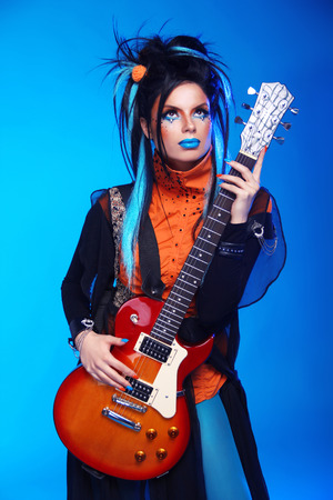 punk rock: Punk rock girl guitarist posing over blue studio background. Trendy model with hairstyle. Model isolated on blue studio background Stock Photo