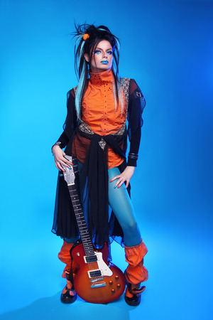 punk rock: Punk rock girl guitarist posing over blue studio background. Trendy model with hairstyle.