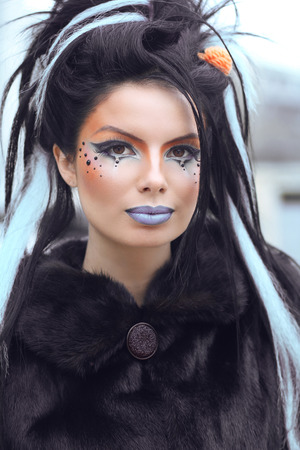 coloring lips: Beauty fashion punk teen girl portrait with art makeup and rock hairstyle. Outdoor
