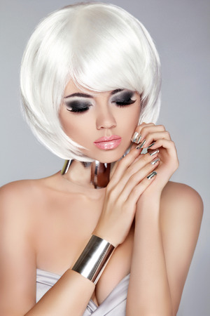 grey nails: Smoky eye makeup. White Bob Hairstyle. Fashion blong girl model. Manicured nails. Silver jewelry. Studio photo of Young woman over grey background. Stock Photo
