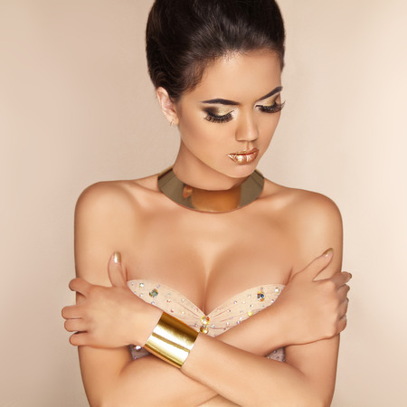 Beautiful Glamor fashion model girl in luxurious golden jewelry.