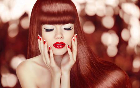 長い髪を持つ美しい女の子。ファッションの女性の肖像画。メイク。手入れの行き届いた爪。健康的な光沢のある赤い髪型。
