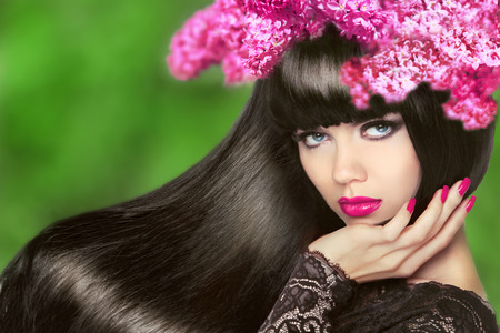 Attractive Brunette Girl with Flowers Long Hair. Healthy Black Hairstyle. Makeup. Manicured nails. Beauty Model Woman isolated on green natural background. Stock Photo