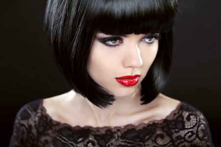 stares: Brunette Woman With Black Short Hair. Haircut. Hairstyle. Fringe. Professional Makeup. Lady isolated on black background.