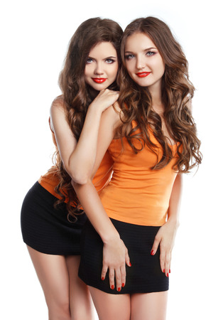 two women hugging: Two attractive girls with long wvy hair and makeup wearing in same clothes isolated on white background