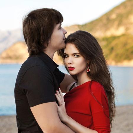 baiser amoureux: Couple romantique dans l'amour à la plage de coucher du soleil. Jeunes mariés jeunes amants heureux embrassant profiter lune de miel vacances. Banque d'images