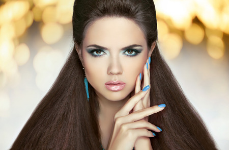 Beautiful model brunette with makeup, long hair. Manicured nails. Hairstyle. Fashion girl over lights holiday background. Фото со стока