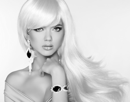 Beautiful blond woman model with long wavy hair. Luxury Jewelry. Glamour concept. Studio Fashion photo.