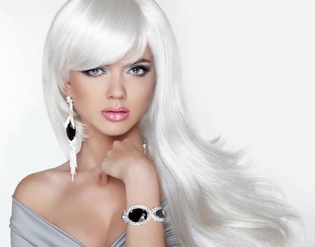 Lang haar. Fashion Blond meisje met witte golvende kapsel. Dure Jewelry.Beauty portret. Aantrekkelijke vrouw model poseren op studio achtergrond.