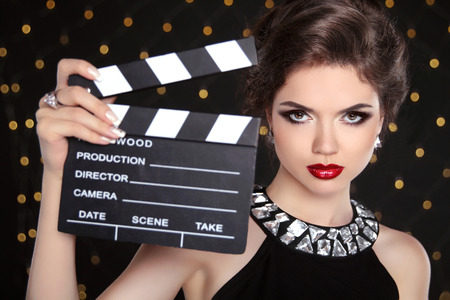 Beautiful brunette woman model holding film clap board cinema. Fashion portrait of girl with makeup, hairstyle and expensive jewelry. Stock Photo
