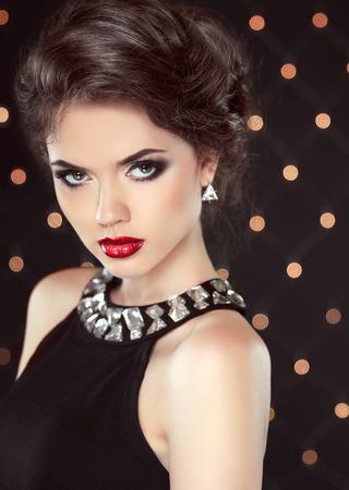 vestido de noche: Encanto de la manera del retrato elegante dama con labios rojos y el peinado más de fondo de las luces. Mujer joven atractiva. Niña linda. Foto de archivo