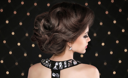 hair styling: Hairstyle. Brunette woman with wavy retro hair styling. Fashion girl model Isolated on black background with lights. Stock Photo