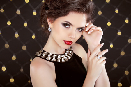Beautiful brunette woman model with makeup and hairstyle in fashion jewels over bokeh lights background. Elegant lady. Stock Photo