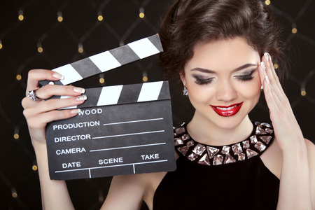 casting: Fashion elegant woman posing with sexy red lips holding cinema clap. Super star model shot. Happy smiling girl.