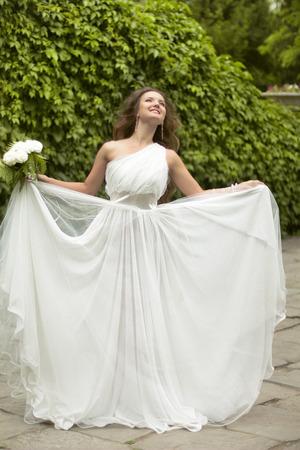voluminous: Happy young bride enjoying wedding day in fashion white dress with voluminous skirt at green park. Stock Photo