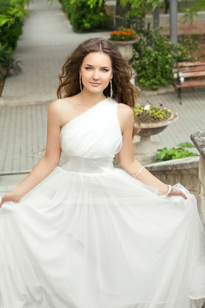 voluminous: Attractive bride with long wavy hair in wedding dress with voluminous skirt at park.