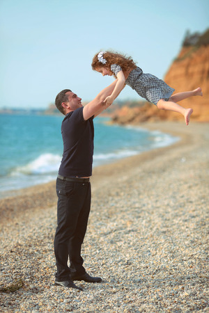 to toss: Father toss up daughter playing together on the beach carefree happy fun smiling lifestyle
