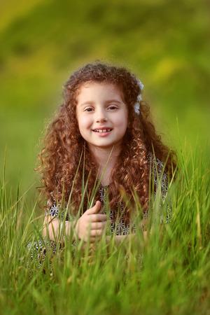 cabello rizado: Retrato de divertida niña sonriente con el pelo rizado en campo de hierba verde en el ocaso. foto al aire libre.