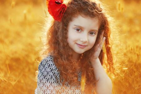 cabello rizado: Hermosa niña sonriente con el pelo rizado en el campo de hierba al atardecer. retrato al aire libre