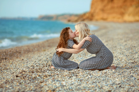 beach kiss: Mother kissing her daughter on the beach. outdoor family portrait. two same look person.