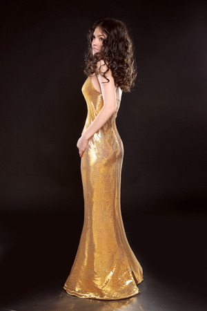 bronzed: Glamour brunette girl in Fashion golden dress isolated on black background. Elegant lady with Long curly hair, beauty makeup, luxury jewelry.