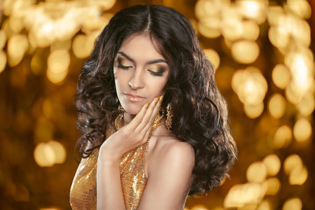 glitter makeup: Fashion brunette girl with Long curly hair, beauty makeup, luxury jewelry. Beautiful attractive young woman in golden dress posing over holiday lights background.
