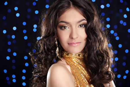 glitter makeup: Fashion brunette girl with Long curly hair, beauty makeup, luxury jewelry. Beautiful attractive young woman in golden dress posing over holiday lights glitter background. Stock Photo