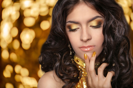 eye makeup: Fashion brunette girl with Long curly hair, beauty eye makeup, luxury jewelry. Beautiful attractive young woman in golden dress posing over holiday lights background.