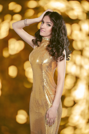 bronzed: Beauty Glamour brunette girl in Fashion golden dress isolated on holiday lights background. Elegant lady with Long curly hair, beauty makeup, luxury jewelry. Stock Photo