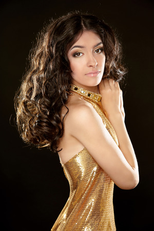 long: Attractive brunette girl with Long curly hair, beauty makeup, luxury jewelry. Beautiful attractive young woman in golden dress isolated on black background.