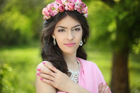 Brunette girl with flower chaplet in green filed wearing in pink dress on green field. Stock Photo